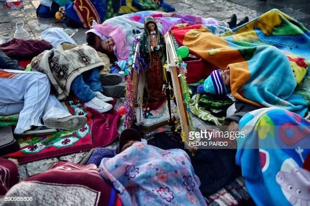 People sleep in the atrium of the Basilica of Guadalupe during the feast of the Virgin of Guadalupe patron saint of Mexico in Mexico City on December...