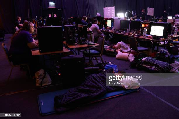 People sleep next to their gaming stations at the start of day three of the epicLAN esport tournament at the Kettering Conference Centre on October...