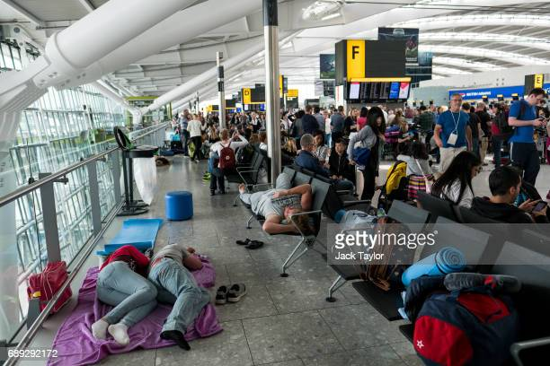 People sleep on a blanket at Heathrow Airport Terminal 5 on May 28 2017 in London England Thousands of passengers face a second day of travel...