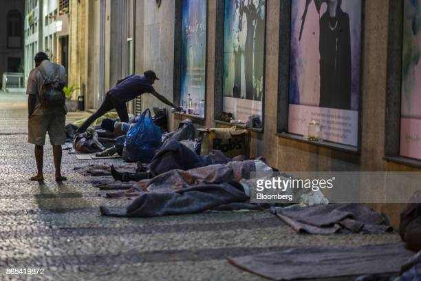 People sleep on a street outside the Public Defender headquarters in Rio de Janeiro Brazil on Thursday Aug 24 2017 According to the World Bank...