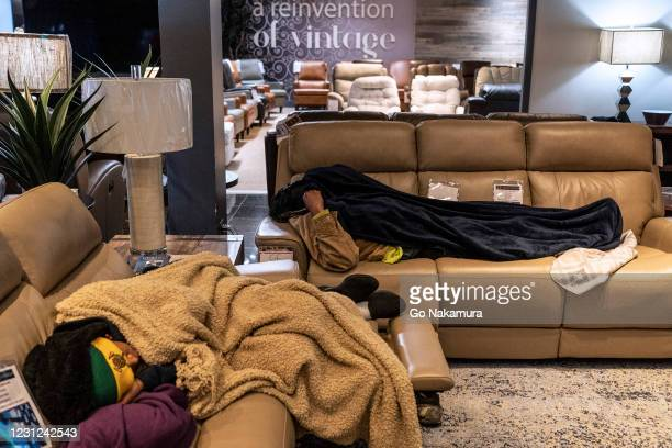 People sleep on couches while taking shelter at Gallery Furniture store which opened its door and transformed into a warming station after winter...