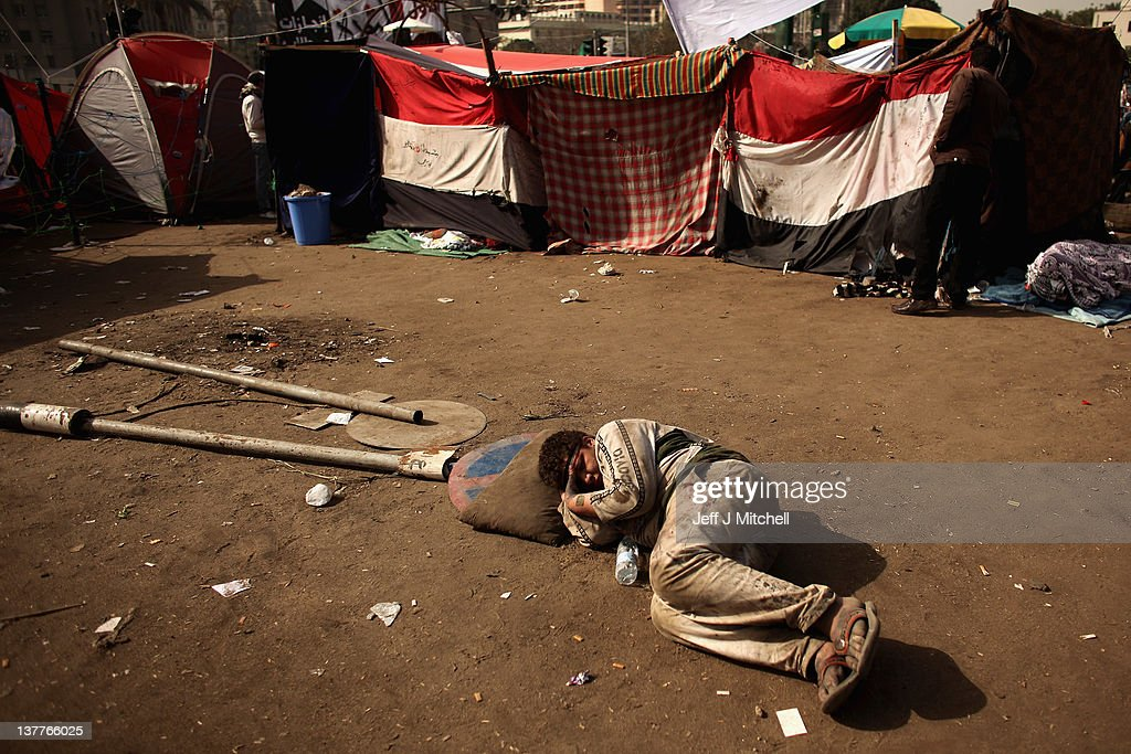 People sleep on the ground in Tahrir Square as crowds continue to gather on January 26, 2012 in Cairo, Egypt. Tens of thousands of Egyptian people gathered yesterday to celebrate the anniversary of the start of the uprising which ended President Hosni Mubaraks rule.