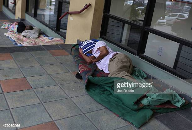 People sleep on the sidewalk a day after Puerto Rican Governor Alejandro Garcia Padilla gave a televised speech regarding the governments $72 billion...