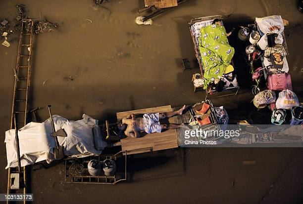 People sleep outdoors with their belongings in the parking lot of a freight yard submerged by floods near where the Yangtze River and Hanjiang River...