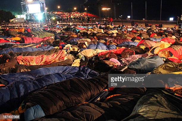 People sleep outside before a ceremony marking the 98th anniversary of Anzac Day at Anzac Cove, in western Canakkale, on April 25, 2013. Anzac Day is...