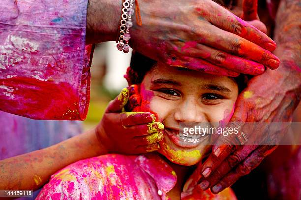 people smearing holi colours on a boy - holi stock pictures, royalty-free photos & images