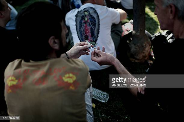 People smoke a joint during a rally to call for the legalization of the use of cannabis in Athens on May 9 2015AFP PHOTO / Angelos Tzortzinis