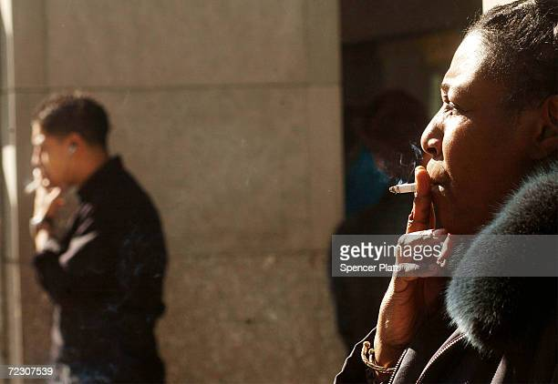 People smoke cigarettes outside of an office building February 19 2002 in New York City As part of his recent budget plan New York Mayor Michael...