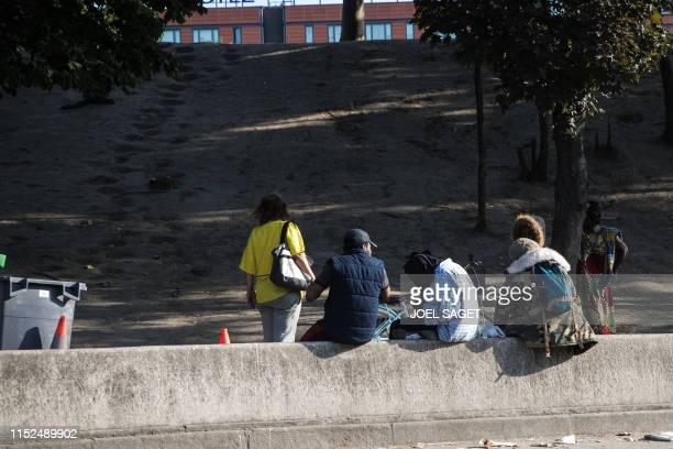 People smoke drugs near the Paris ring road on the socalled 'Crack Hill' in Porte de la Chapelle in Paris on June 27 2019