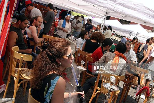 People smoke hookah pipes at an outdoor cafe at the Annual ArabAmerican and NorthAfrican street festival July 10 2004 in New York City