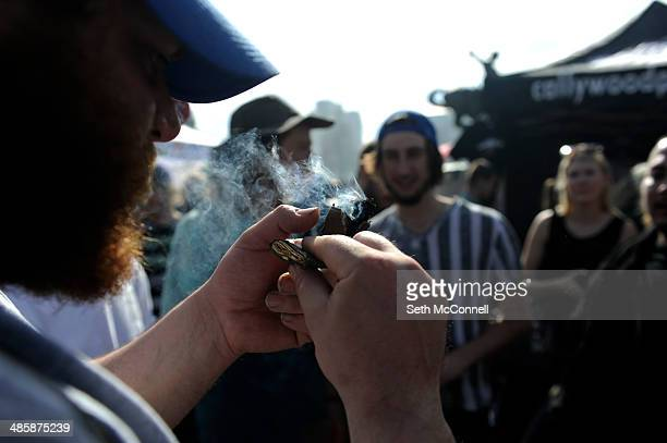 People smoke pot as the clock strikes 420 during the 420 Rally at Civic Center Park in Denver Colorado on April 20 2014