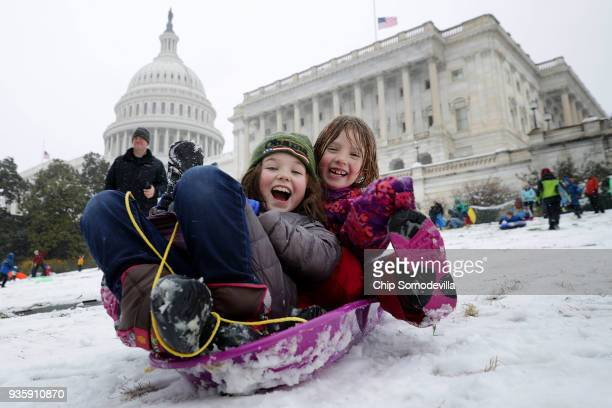 People snow sled on the grounds of the US Capitol March 21 2018 in Washington DC An early spring storm brought several inches of snow to the East...