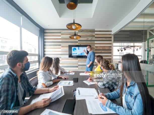 pessoas se distanciando socialmente e usando máscaras faciais em uma reunião de negócios no escritório - reunião de equipe - fotografias e filmes do acervo