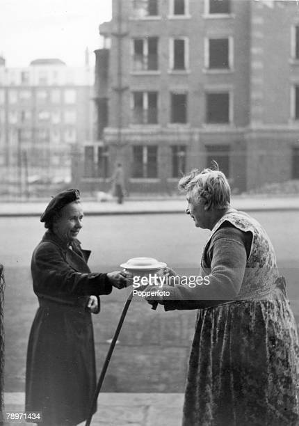1950's Great Britain A hot meal container is handed over to an elderly woman outside her home by a member of the Women's Voluntary Service as part of...