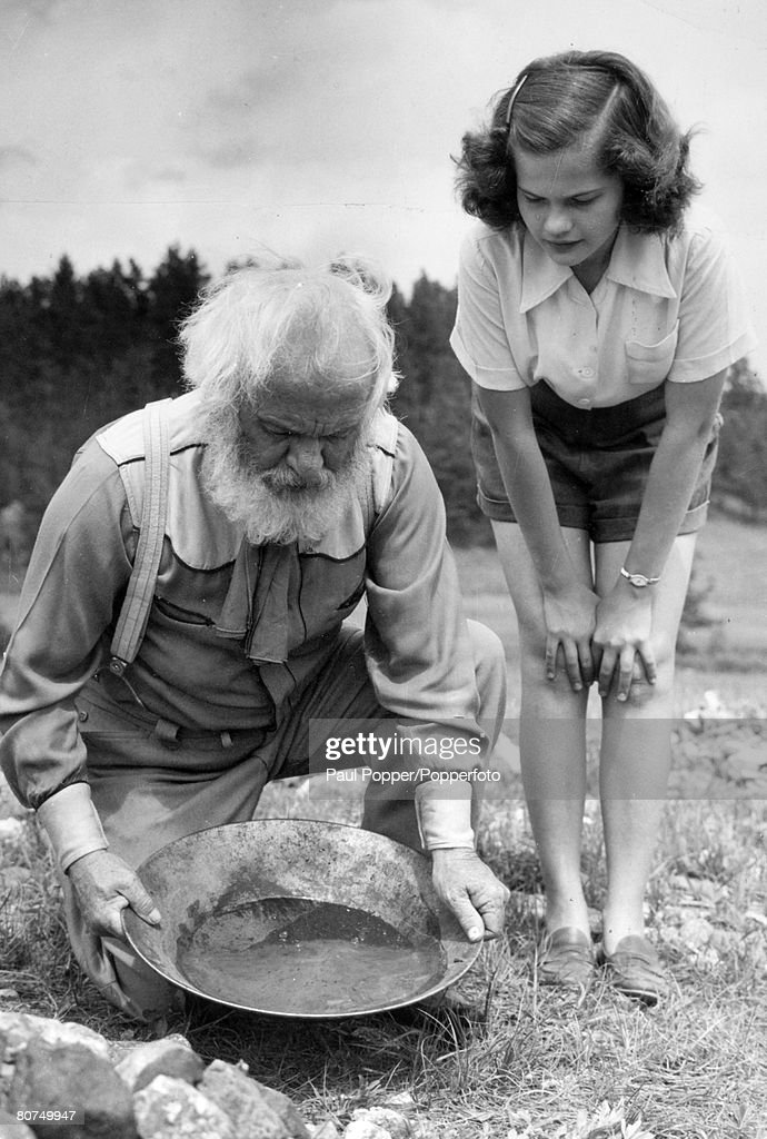 People Social History. pic: circa 1940's. Black Hills, South Dakota, USA. An old gold prospector seen prospecting for gold with an interested spectator alongside. : News Photo