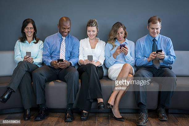 People social networking on their phones at the office