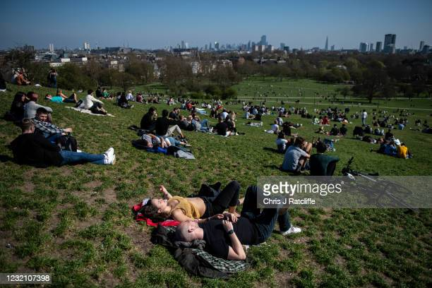 People socialise in the sunshine on Primrose Hill on April 4, 2021 in London, England. Earlier this week, the UK government eased rules on...