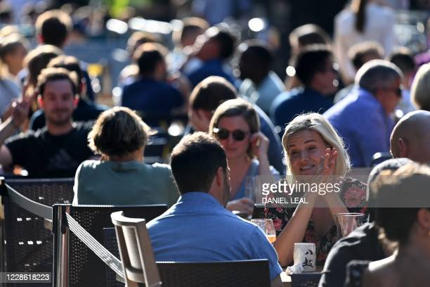 People socialize in the late summer sunshine at outside tables in Soho central London on September 20 2020 as the British government consider fresh...