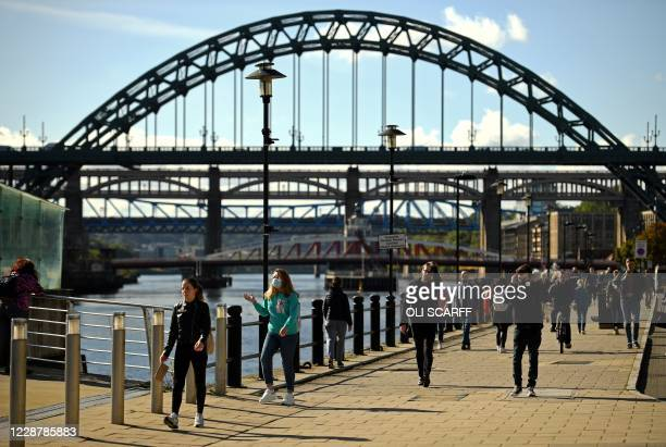 People, some wearing a face mask or covering due to the COVID-19 pandemic, walk along the bank of the River Tyne, near the Tyne Bridge, in Newcastle,...