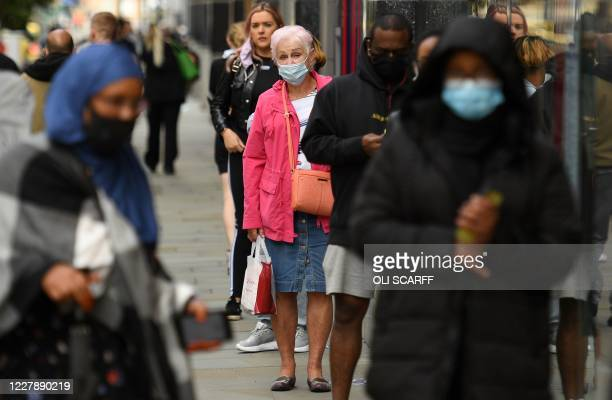 People, some wearing face masks or covering due to the COVID-19 pandemic, queue to enter a shop in Manchester, northwest England on August 3...