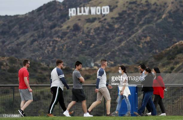 People, some wearing face masks, walk in Griffith Park with the Hollywood sign behind them on March 22, 2020 in Los Angeles, California. California...
