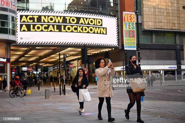 People, some wearing face masks, walk through the shopping area in the city centre of Manchester, north west England on October 8, 2020. - Pubs and...