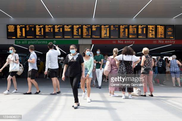 People, some wearing masks to prevent the spread of Covid-19 and some not, leaving the platforms of Leeds train station with the departures and...