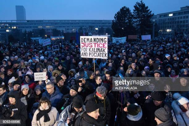 People some with placards gather at the Freedom Square during a silent protest march to pay tribute to murdered Slovak journalist Jan Kuciak and his...