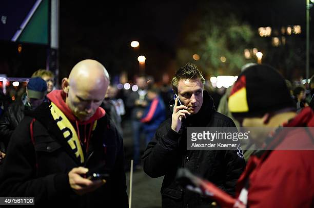 People speak on their mobile phones shortly after the match between Germany and the Netherlands was cancelled following a bomb alert at the HDIArena...