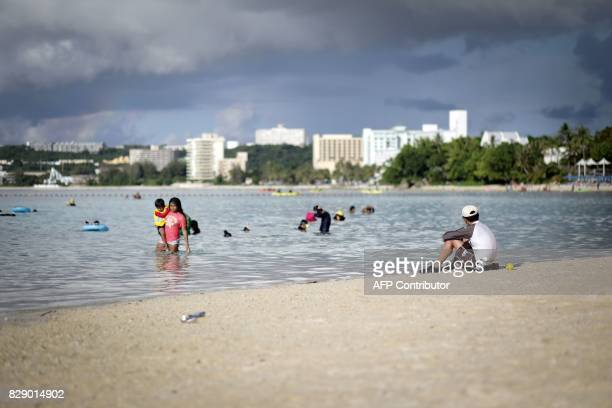 People spend their afternoon along Tumon beach in the city of Tamuning on the island of Guam on August 10 2017 Guam's governor on August 10 said the...