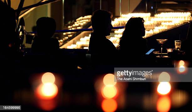 People spend time after switchoff the lights to recognize the Earth Hour at Hilton Fukuoka Seahawk on March 23 2013 in Fukuoka Japan Businesses and...