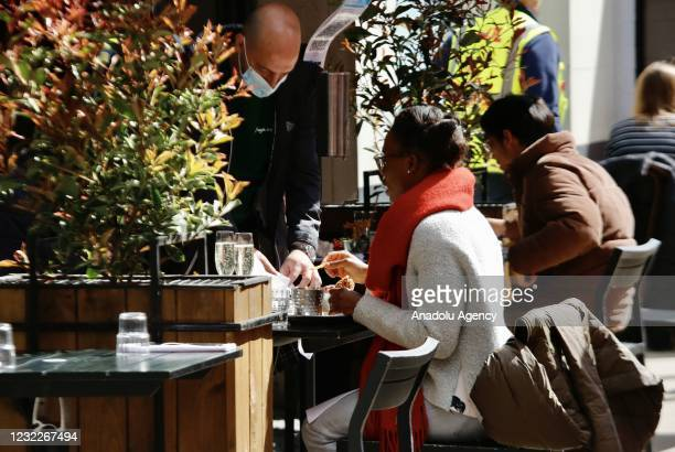 People spend time at open air of a cafe after the country enters the second stage of the government's roadmap out of the countryâs third nationwide...