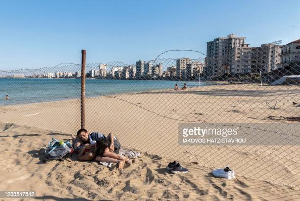 People spend time at the seaside in the fenced-off area of Varosha in Famagusta town in the self-proclaimed Turkish Republic of Northern Cyprus of...