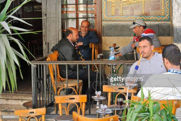 People spend time in a cafe on April 7 2017 in Damascus Syria The United States attacked on Syrian military base