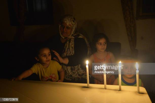 People spend time in the dark during power cuts due to the fuel shortage and problems in the supply of fuel, which is traded in dollars, in Beirut,...