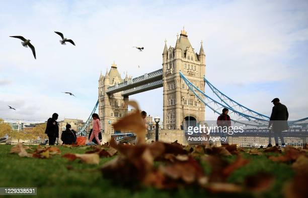 People spend time near the Tower Bridge amid fallen leaves during autumn season in London, United Kingdom on October 28, 2020.
