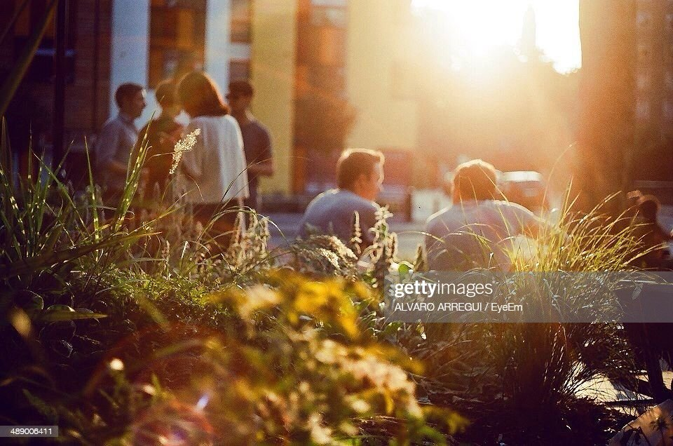 People spending leisure time in city during sunset : Stock Photo