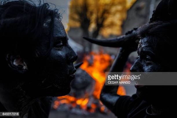 People sporting horns on their heads and grease on their faces to represent 'Diablos de Luzon' perform during the carnival in Luzon near Guadalajara...