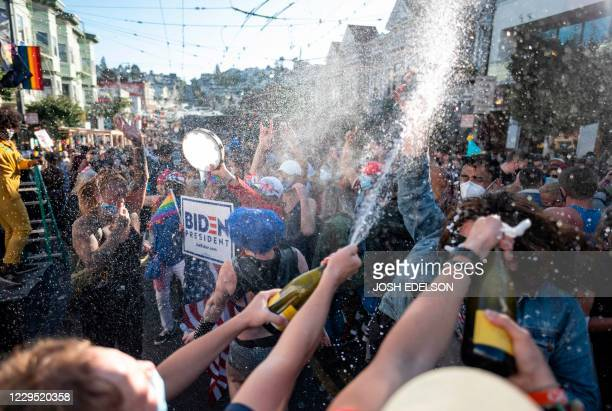 People spray champagne as they celebrate Joe Biden being elected President of the United States in the Castro district of San Francisco California on...