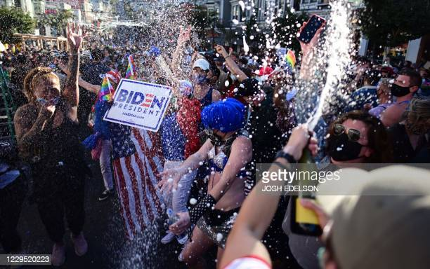People spray champange in the street and dance along with other demonstrators in celebration for Joe Biden getting elected President of the United...