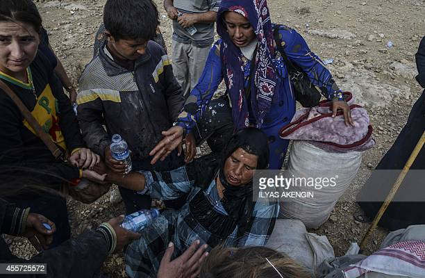 People spray water on a woman suffering from heat as Syrian Kurds cross the border between Syria andTurkey near the southeastern town of Suruc in...