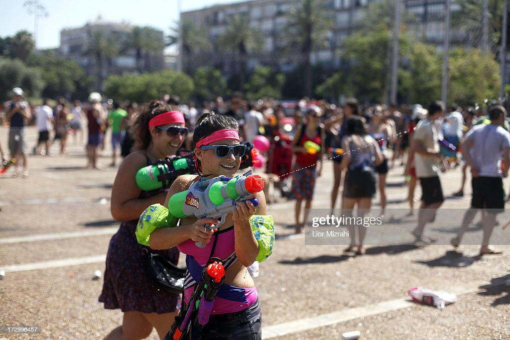 People spray water with a water gun during the annual water fight at Rabin Square July 5, 2013 in Tel Aviv, Israel. Hundreds of Israelis and tourists took part in this ninth annual water fight.