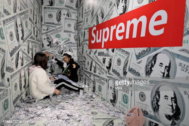 People sprinkle sheets simulating paper money at a stressrelief museum on November 18 2019 in Suzhou Jiangsu Province of China