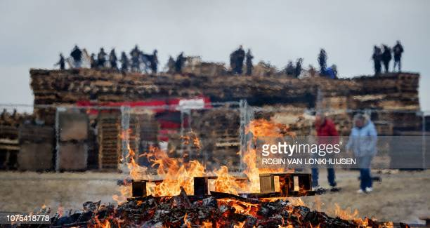 People stack wooden pallets as they build a bonfire for the New Year on the beach of Scheveningen on December 27 2018 Two dutch villages compete in...