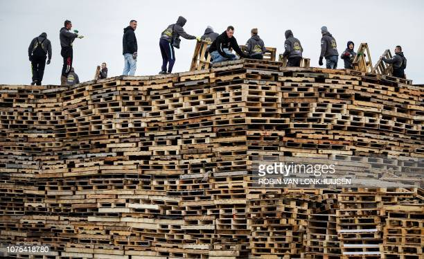 TOPSHOT People stack wooden pallets as they build a bonfire for the New Year on the beach of Scheveningen on December 27 2018 Two dutch villages...