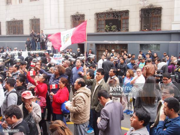 People stage a demonstration in support to former Peruvian President Ollanta Humala while a vehicle transports him and his wife Nadine Heredia toward...