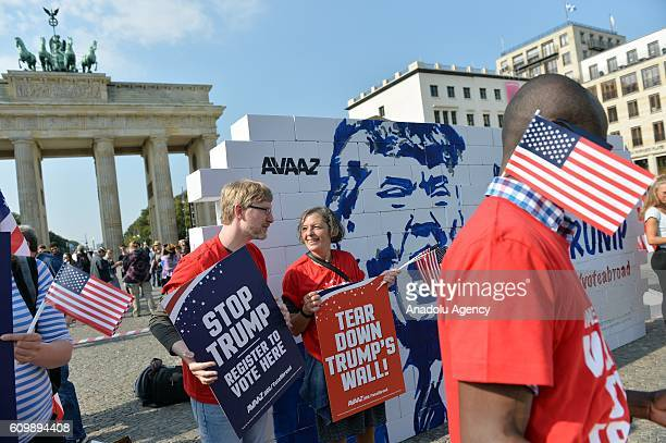 People stage a protest where they are tearing down a so called 'Trump's wall of hate' as part of a demonstration against US Republican presidential...