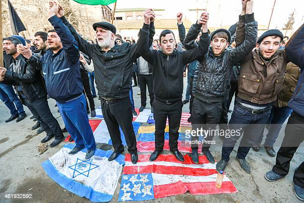 People stamp the flags of France Israel and the United States during a rally in the village of Nardaran to protest against cartoons of the Prophet...