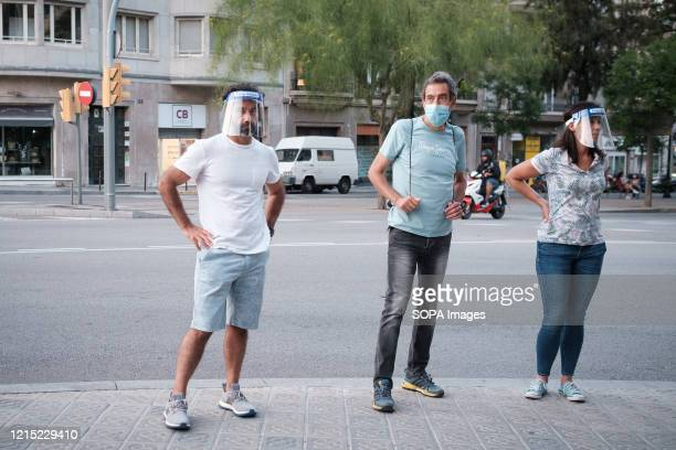 People stand along the street while wearing face masks as a preventive measure during the First Day of Phase 1 The measures of confinement in Spain...