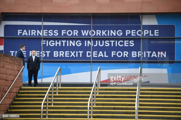 People stand alongside a hoarding with a political message at the Manchester Central convention centre in Manchester on October 1 the first day of...